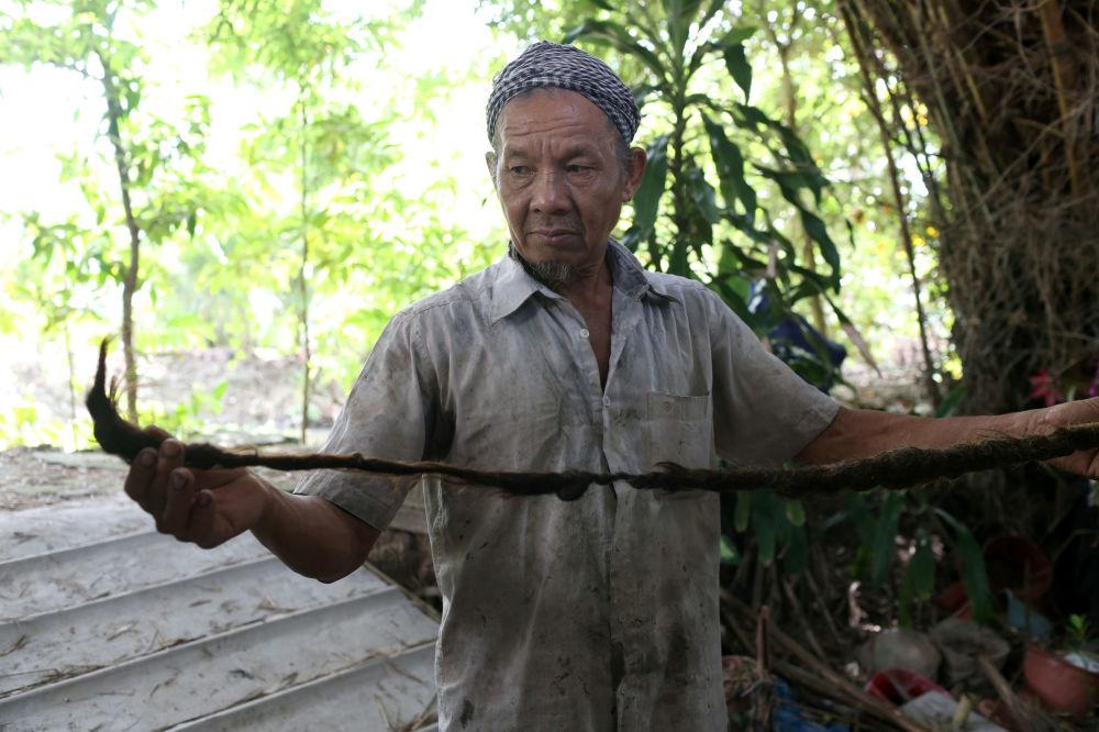 老人的兒子展示父親的5米長辮