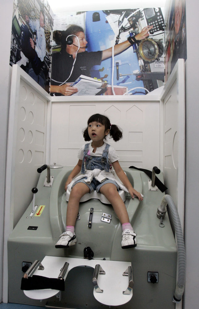 韓國首爾,在「太空體驗」展覽上,一個小女孩在「太空船廁所」里