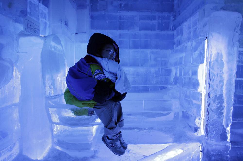韓國首爾,在「冰之畫廊」展覽上,一個小男孩在冰馬桶上