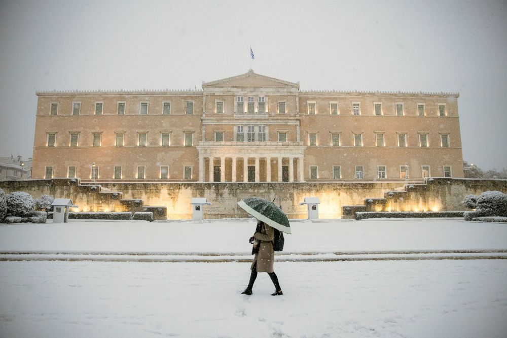 希臘雅典,一名女子打著傘從議會大樓前走過。