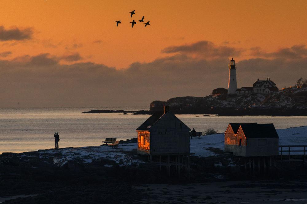 緬因州,日出時參觀南波特蘭漁夫角(Fishermen's Point)的遊客。