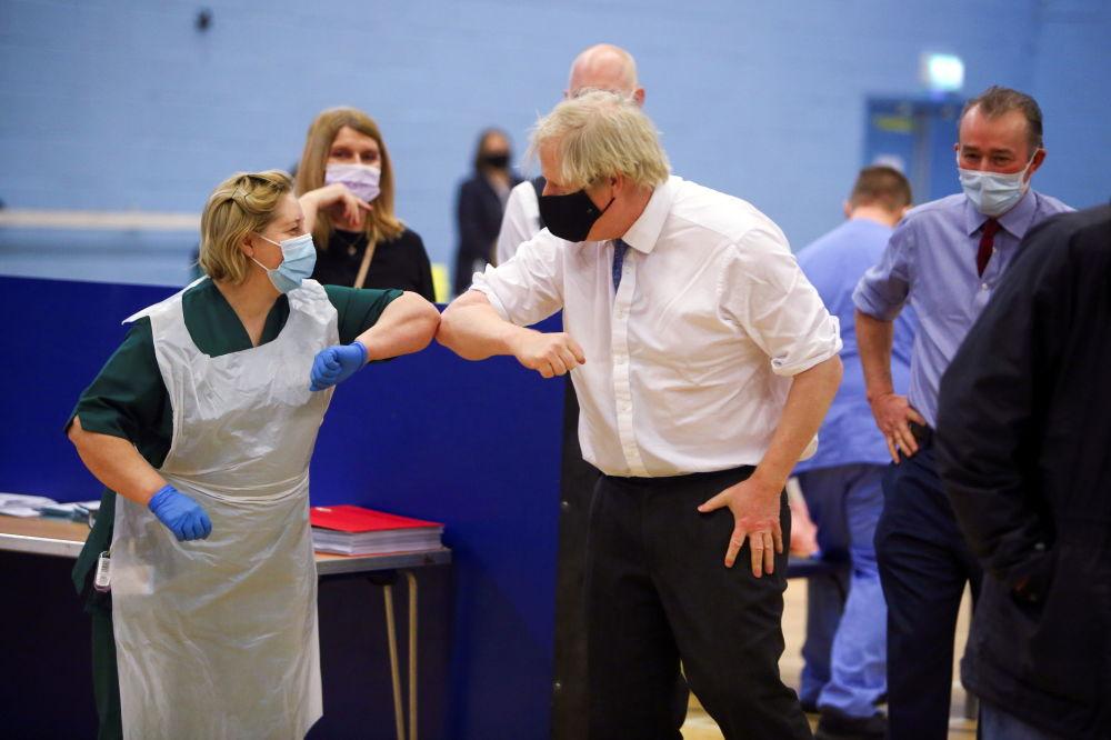 英國首相約翰遜在康布拉鎮新冠疫苗接種中心致敬值守女護士。