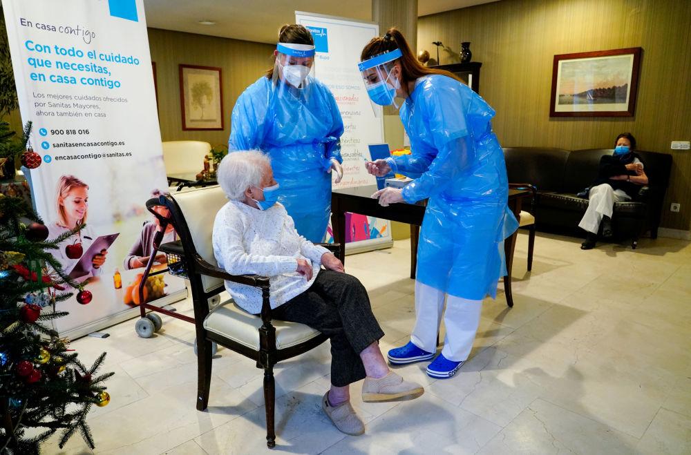 西班牙馬德里敬老院工作人員陪護感染老人接種疫苗。