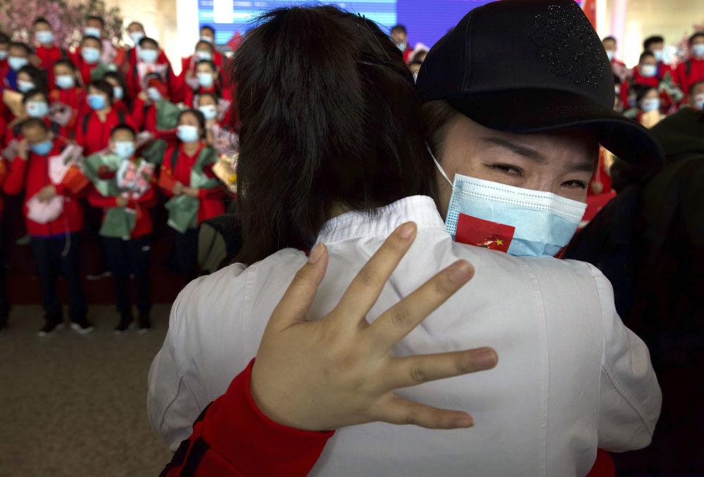 中國女醫師在武漢天河機場與抗疫戰友道別。