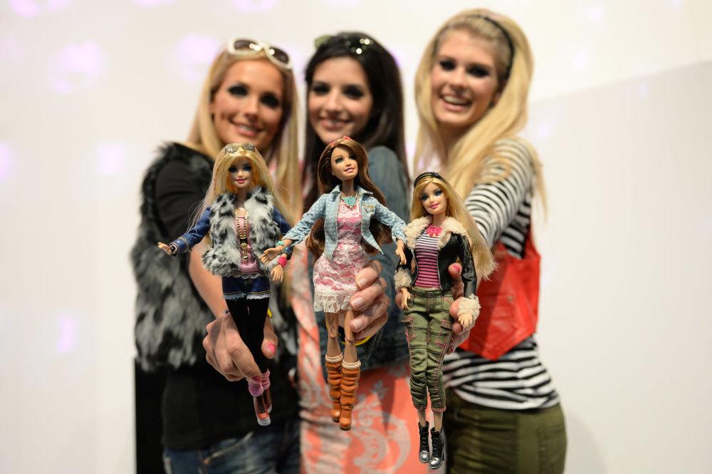 在紐倫堡國際玩具展的美泰公司的展台上,模特與穿著相似服裝的芭比娃娃合影。