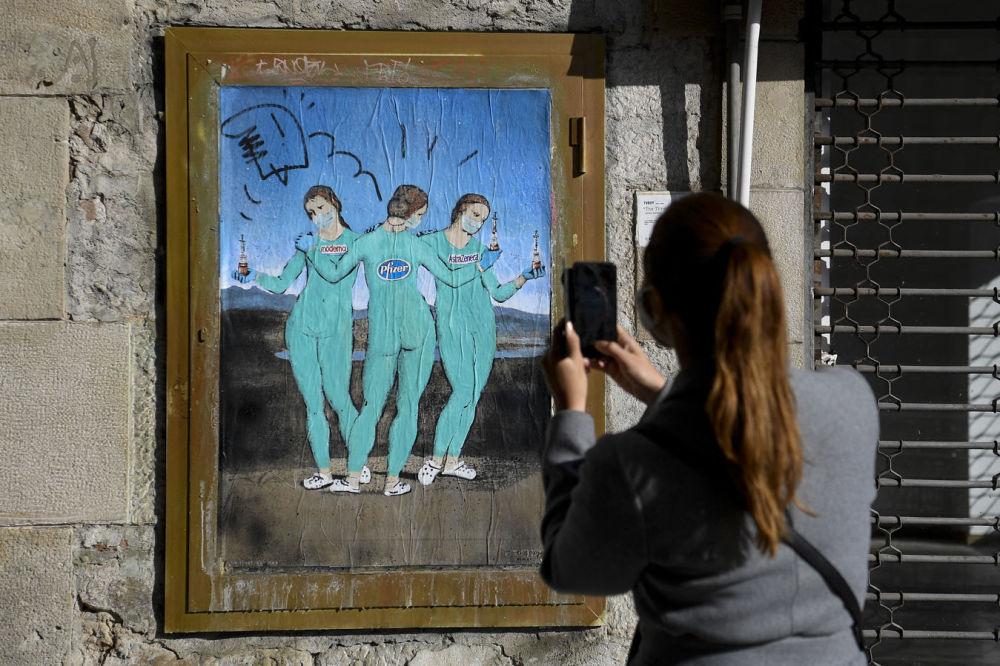 巴塞羅那,意大利街頭藝術家TvBoy的塗鴉《三種疫苗》,儼如拉斐爾的名畫《美惠三女神》。