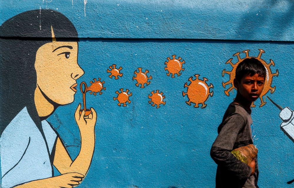 印度孟買,一個男孩從塗鴉前走過。