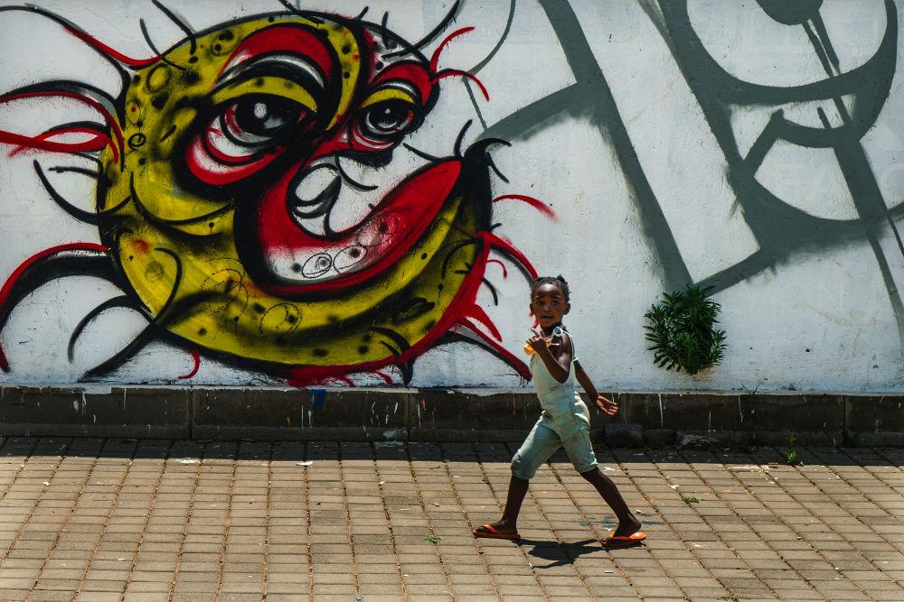 南非索韋托,一個孩子站在繪有新型冠狀病毒的塗鴉牆前。