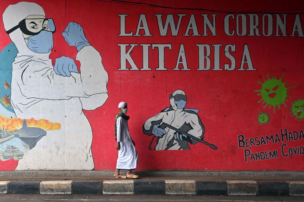 印度尼西亞雅加達,一名男子從塗鴉牆前經過。