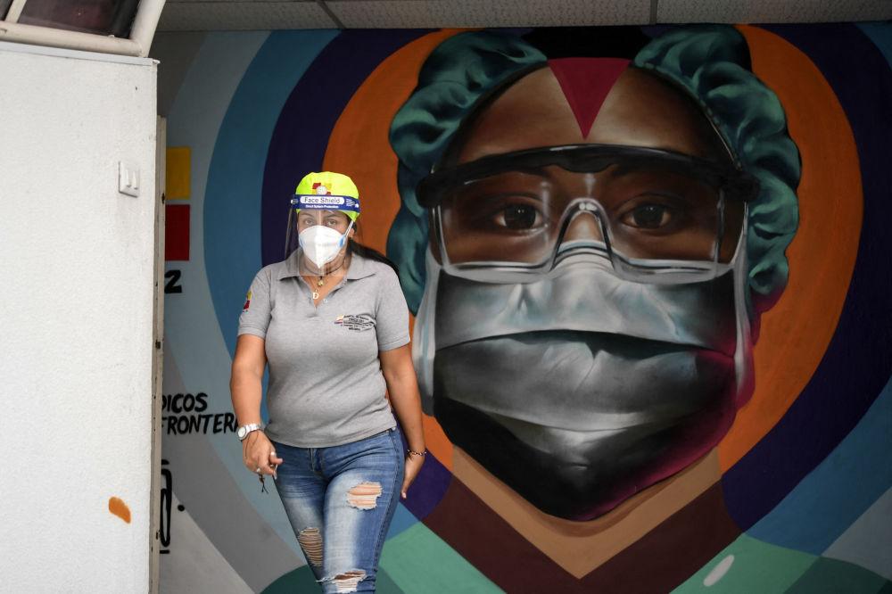 委內瑞拉加拉加斯,醫護人員戴著口罩從塗鴉牆前走過。