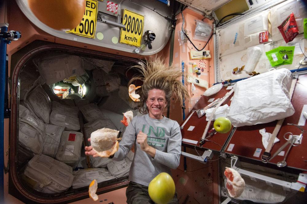 美國航天員凱倫·尼伯格在國際空間站內收集懸浮的水果。