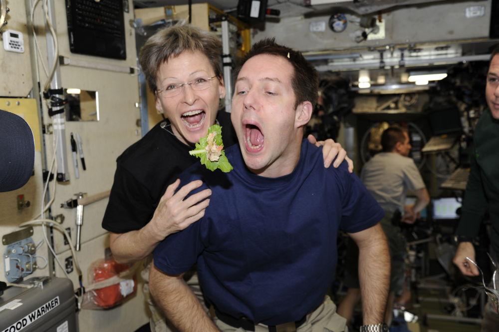 法國航天員托馬·佩斯克與美國航天員威特森在國際空間站艙內就餐。