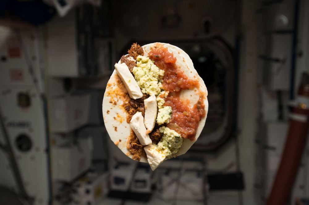 美國航天員提姆·科普拉在國際空間站內進餐。