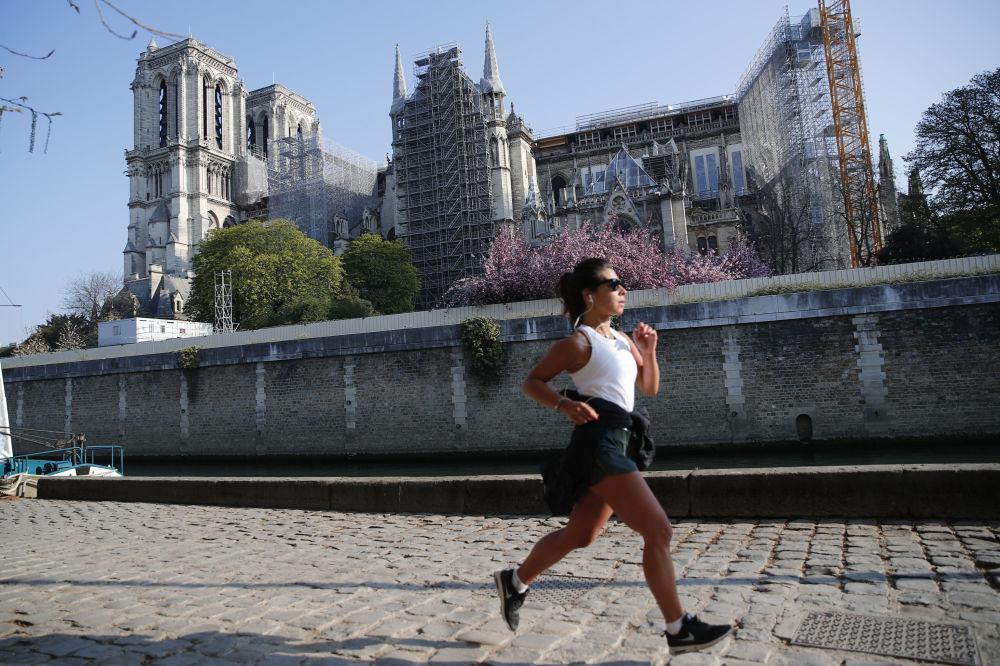 一個姑娘從巴黎聖母院前跑步經過。
