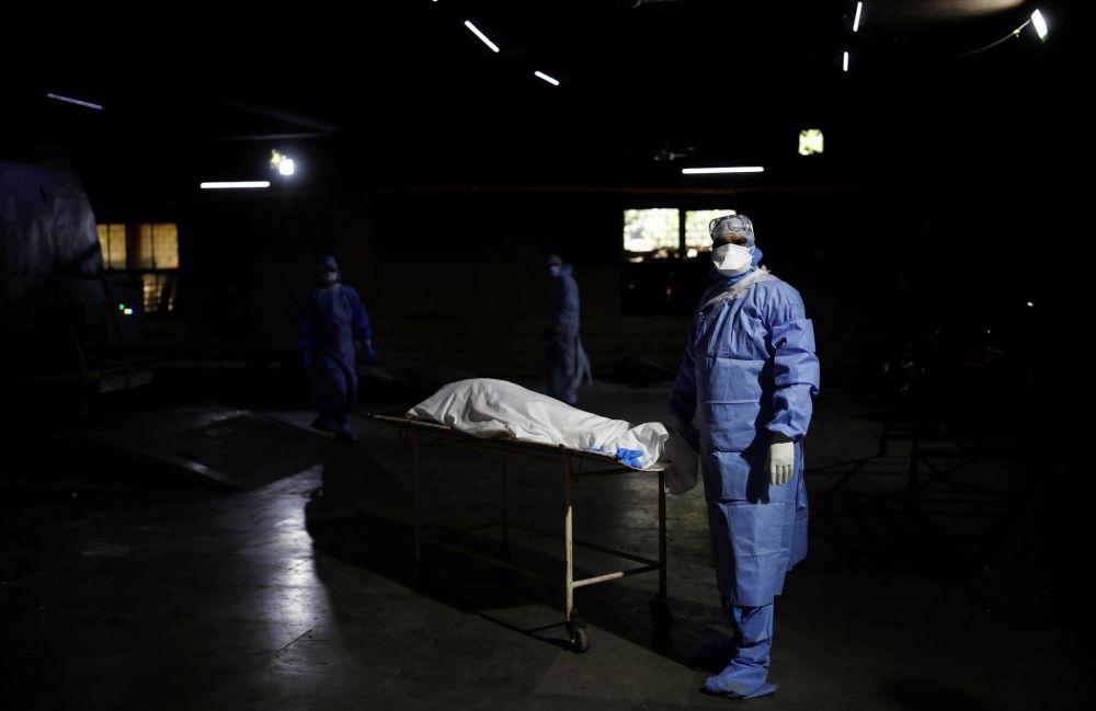 新德里醫務人員正在將新冠死者推往焚屍爐。