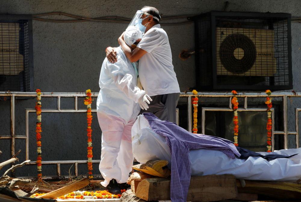 新德里居民在火葬場送別去世者家屬。