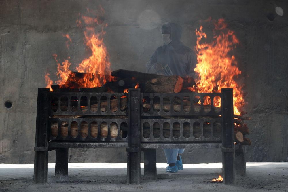 新德里火葬場工人觀察焚屍爐。