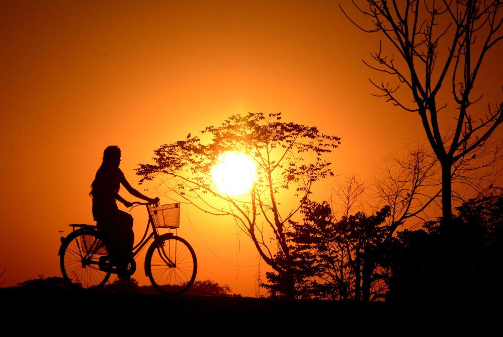 印度女孩在夕陽下騎行。