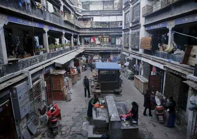 Тибетские женщины стирают одежду во внутреннем дворе в старой части Лхасы