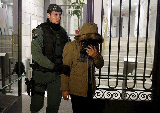 一名女嫌疑人和一名西班牙警官正走出中國工商銀行馬德里分行