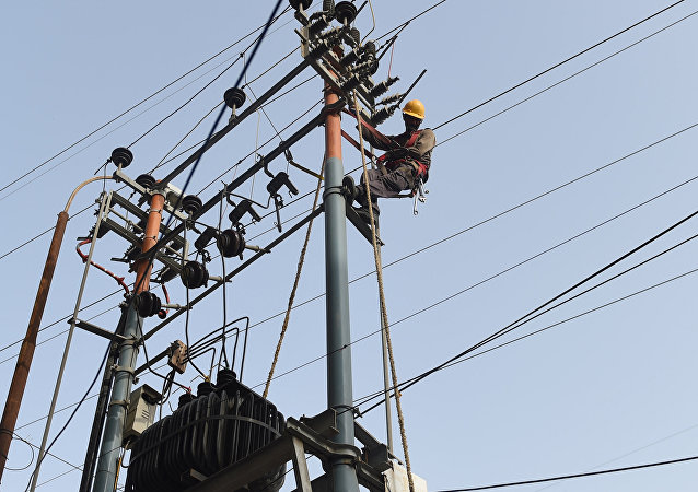 Pakistani technicians of the Karachi Electric Corporation work on a high voltage line in Karachi