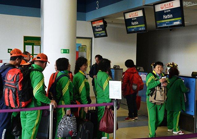 Пассажиры у стойки регистрации китайской авиакомпания Sichuan Airlines на рейс до Харбин в международном аэропорту Владивостока