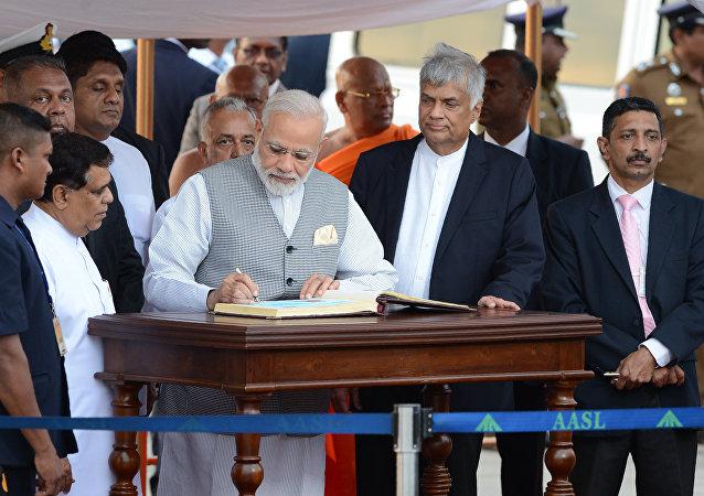 India's Prime Minister Narendra Modi (C) is watched by Sri Lankan Prime Minister Ranil Wickremesinghe (3R)