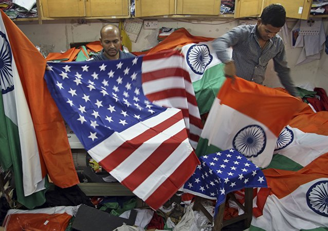 Indian men fold the U.S. and Indian flags at a shop in Mumbai, India