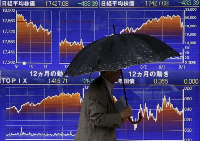 一名男性在日本證券指數走向的電子顯示屏前走過。