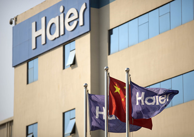 Haier and Chinese flags fly outside of a Haier factory