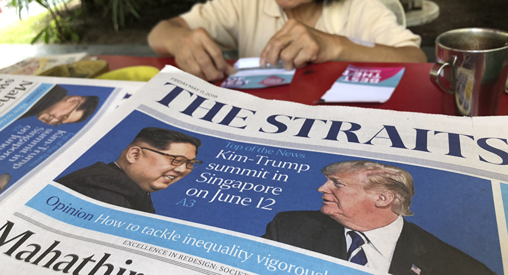 A news vendor counts her money near a stack of newspapers with a photo of U.S. President Donald Trump, right, and North Korea's leader Kim Jong Un on its front page
