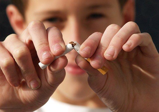 Молодой человек ломает сигарету