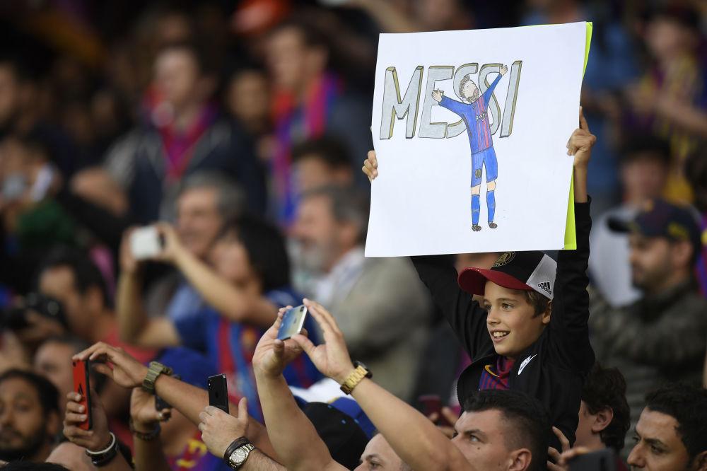 巴塞羅那。在巴塞羅那隊和皇家馬德里隊比賽前,拿著印有巴塞羅那隊前鋒梅西肖像的海報的小球迷。