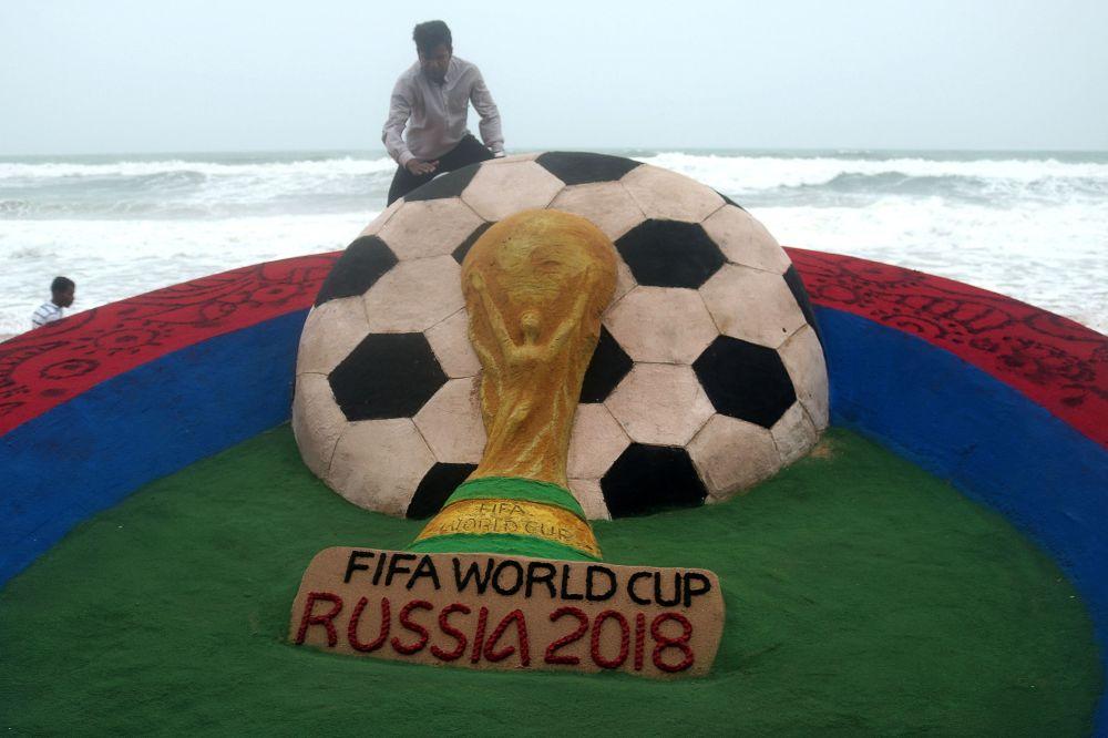 藝術家蘇達爾尚·帕特納伊克在印度「普里」海灘上對和俄羅斯世界杯足球賽有關的沙雕進行最新調整。