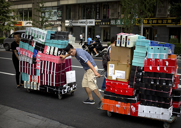 Workers pull carts loaded with shoes made by Nike and other Chinese and foreign shoe manufacturers along a street in Beijing