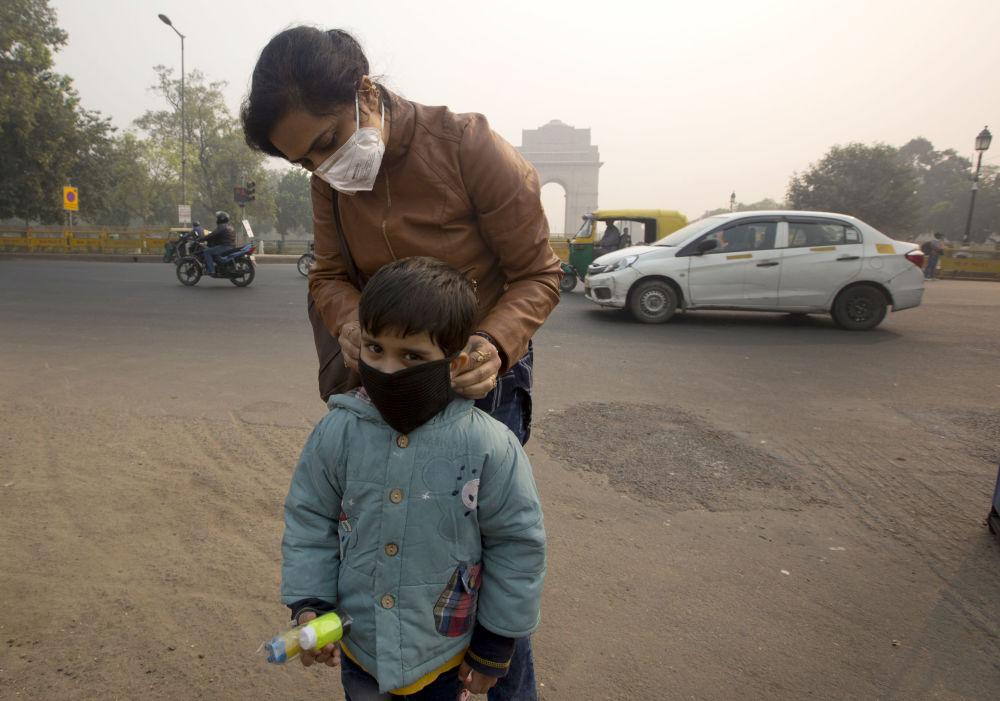母親給兒子戴上面具,以免使他吸入霧霾,新德里,印度