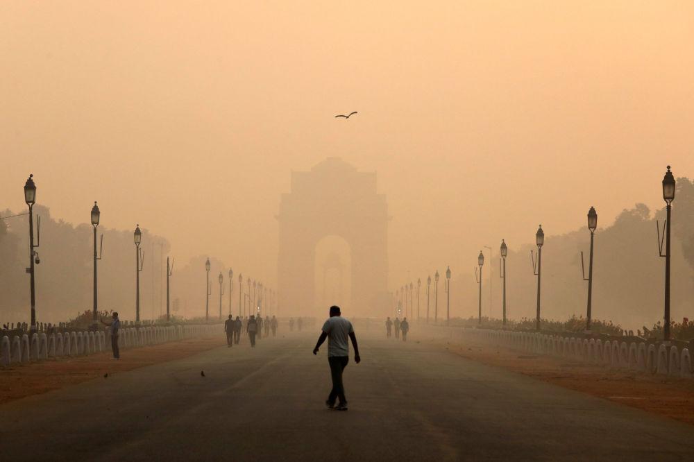 被霧霾籠罩的「印度門」旁的男子,新德里