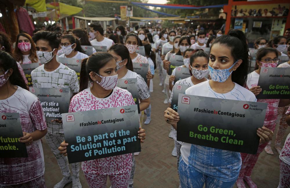 在舉行保護印度新德里的生態環境的活動中,時尚專業的大學生戴著防護面具