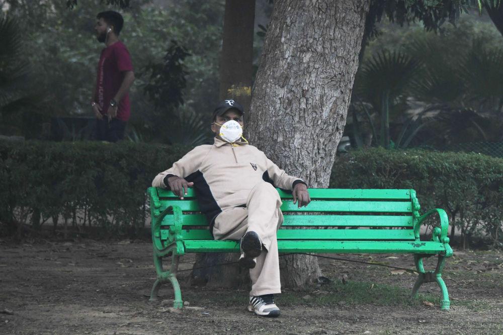 戴著面具面對霧霾的男子,印度,新德里