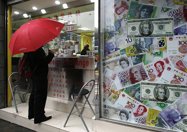 A man stands beside a collage of copies of Chinese RMB, U.S. dollar and other foreign bills at a money exchange store in Hong Kong