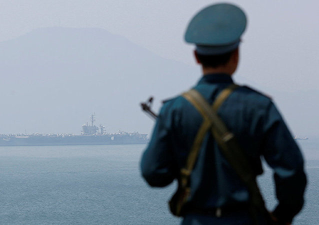 A Vietnamese soldier keeps watch in front of U.S. aircraft carrier USS Carl Vinson after its arrival at a port in Danang, Vietnam.