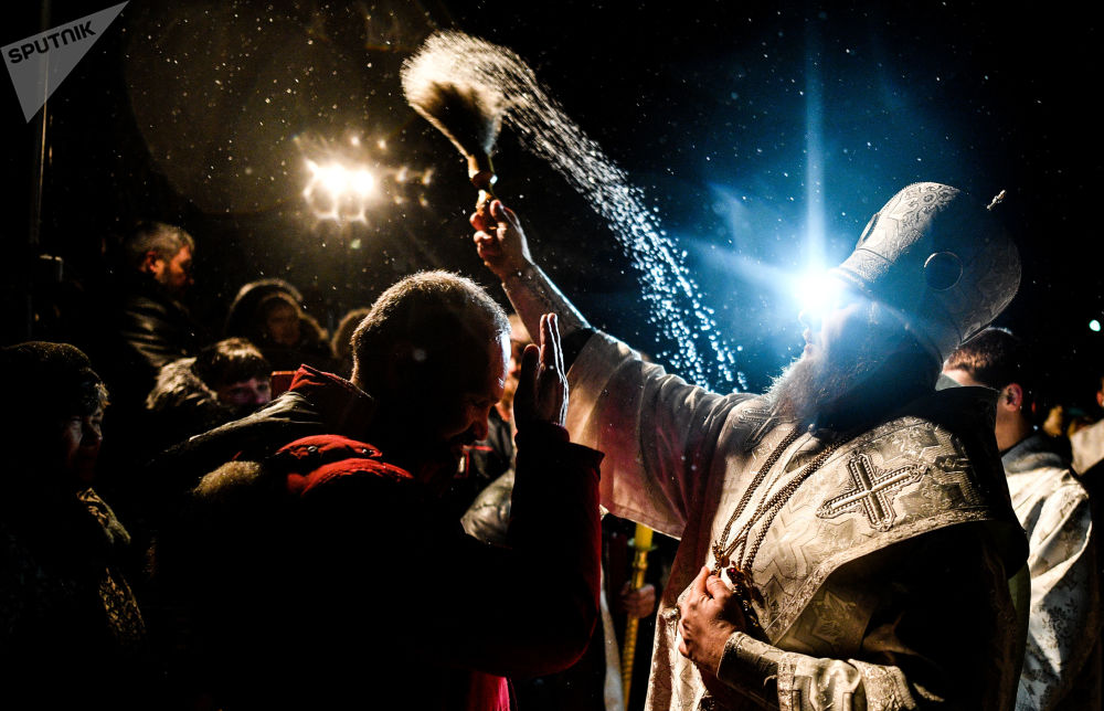 神父在佩列斯拉夫爾 - 扎列斯基為主顯節沐浴參加者灑聖水