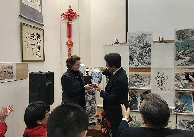 由俄羅斯女畫家安娜∙多琴科把自己繪制的瓷器贈給出席展覽會的中國駐俄羅斯大使