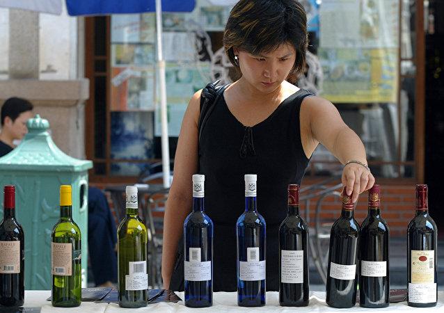 Женщина выбирает вино в магазине. Шанхай.