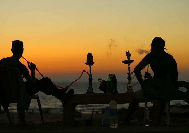 Молодые люди во время курения кальяна