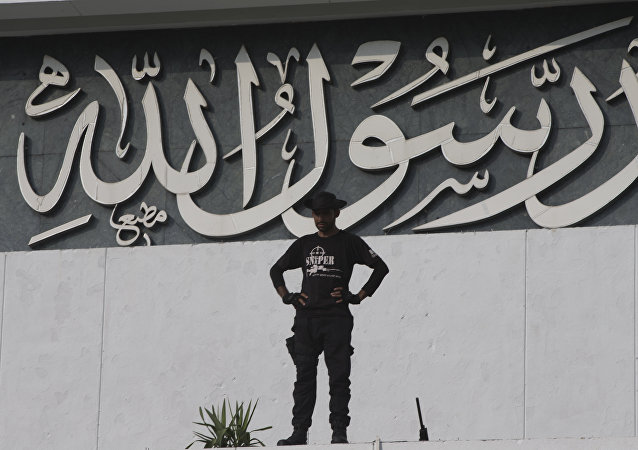 A Pakistani police commando stands guard before Quranic description messenger of God. written on the building of the National Assembly during a session in Islamabad, Pakistan