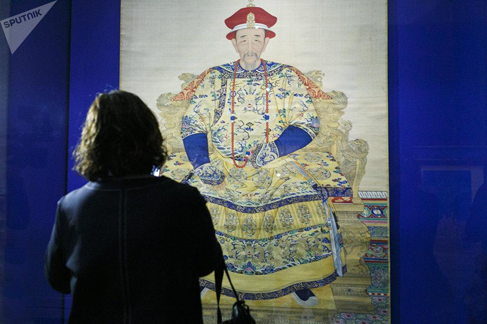 一名女參觀者在看乾隆皇帝的肖像