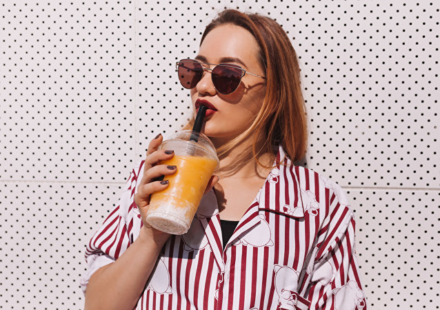 Девушка пьет напиток из пластикового стакана