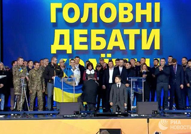澤倫斯基同波羅申科在辯論中下跪