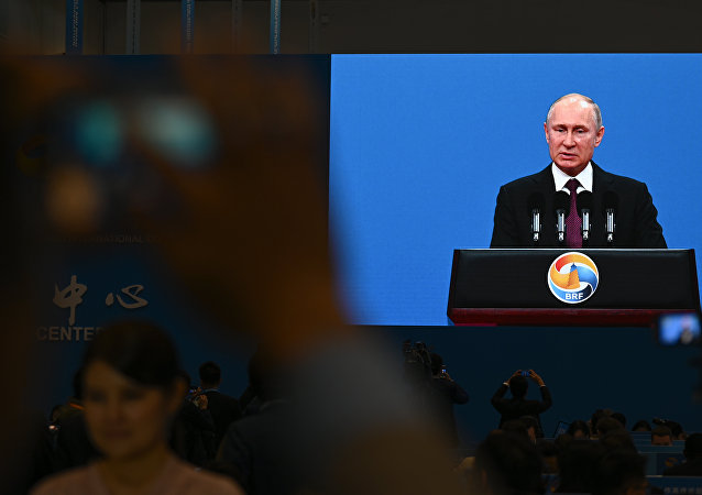 A video screen shows Russian President Vladimir Putin speaking during the opening ceremony of the Belt and Road Forum